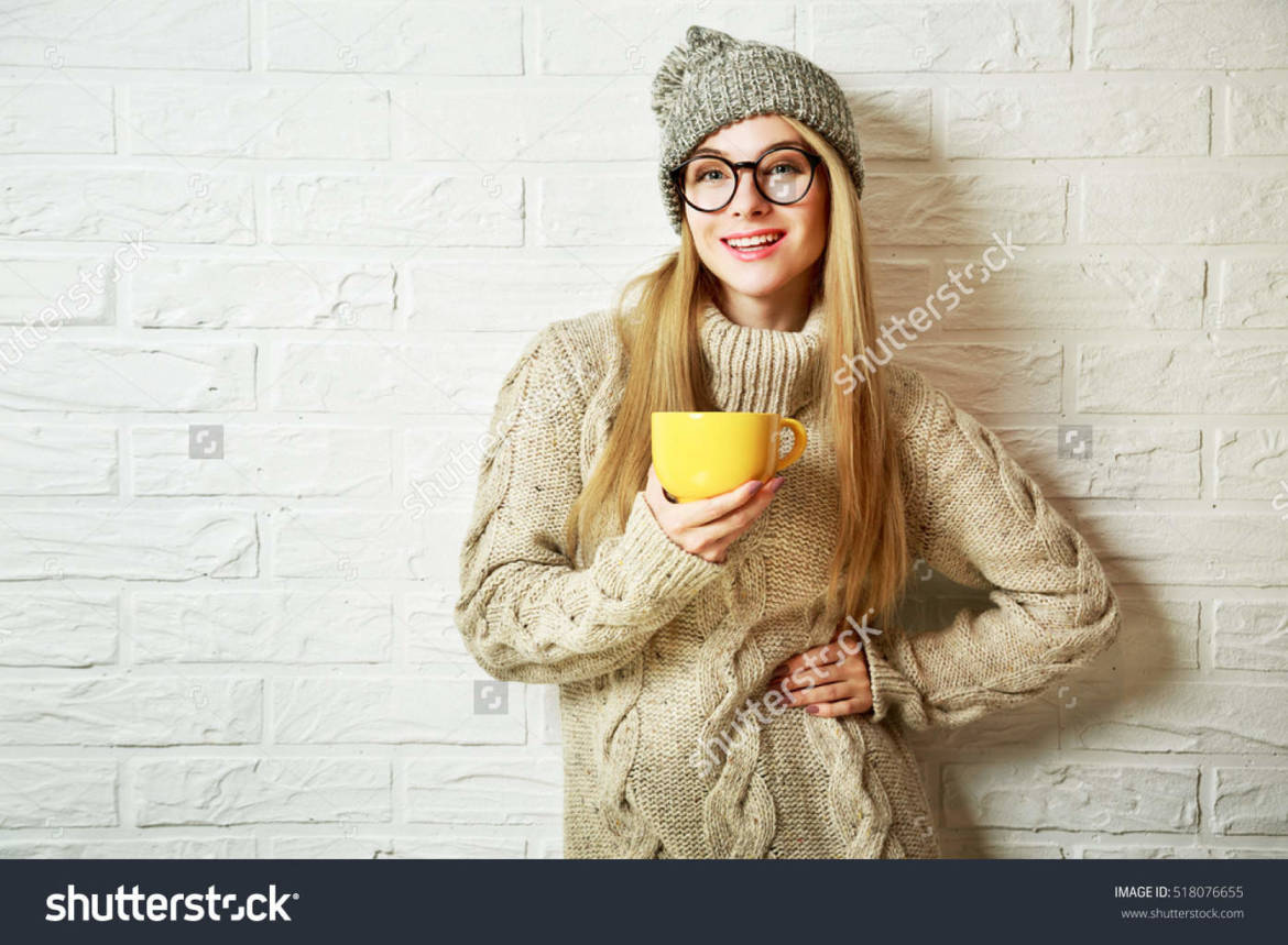 stock-photo-happy-fashion-hipster-girl-in-knitted-sweater-and-beanie-hat-with-a-mug-in-hands-smiling-nice-518076655.jpg