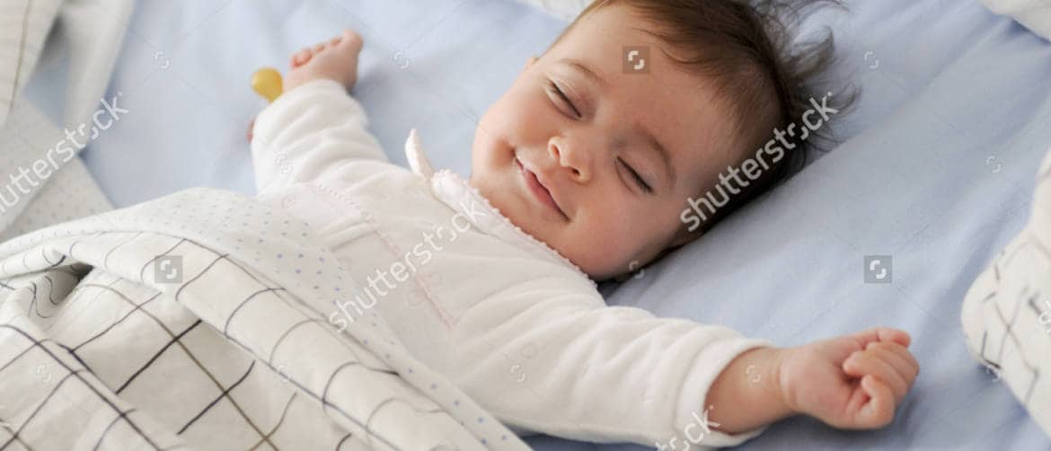 stock-photo-smiling-baby-girl-lying-on-a-bed-sleeping-on-blue-sheets-420756877-1.jpg